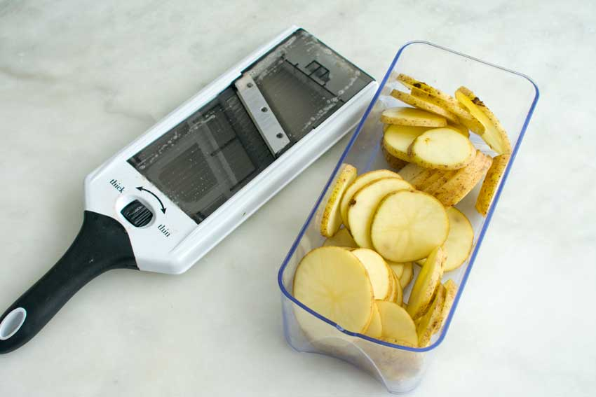 Slicing the potatoes with a mandoline