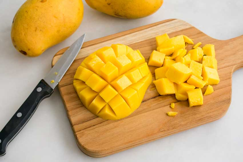 Cutting up the mangoes so they can be pureed