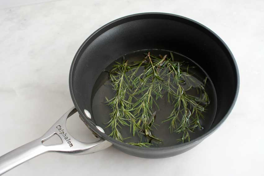 Steeping the rosemary sprigs in the simple syrup