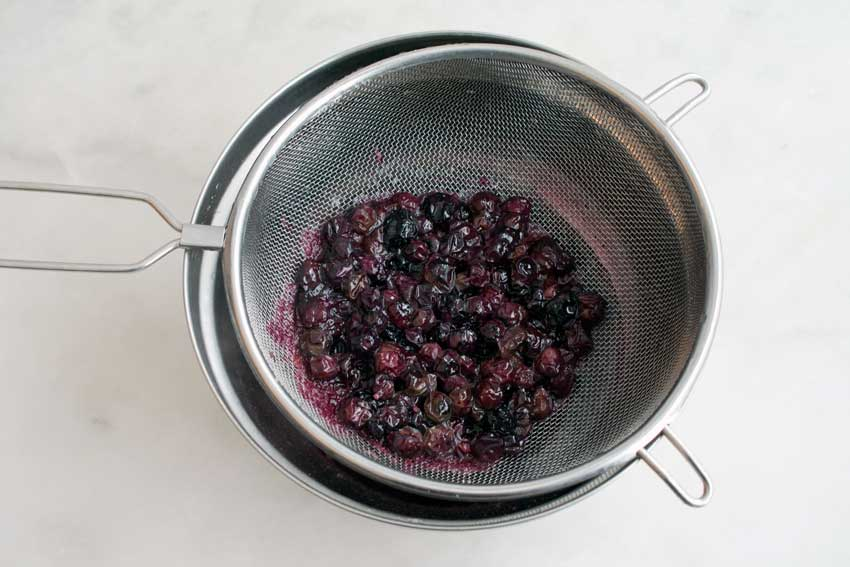 Straining the blueberry syrup