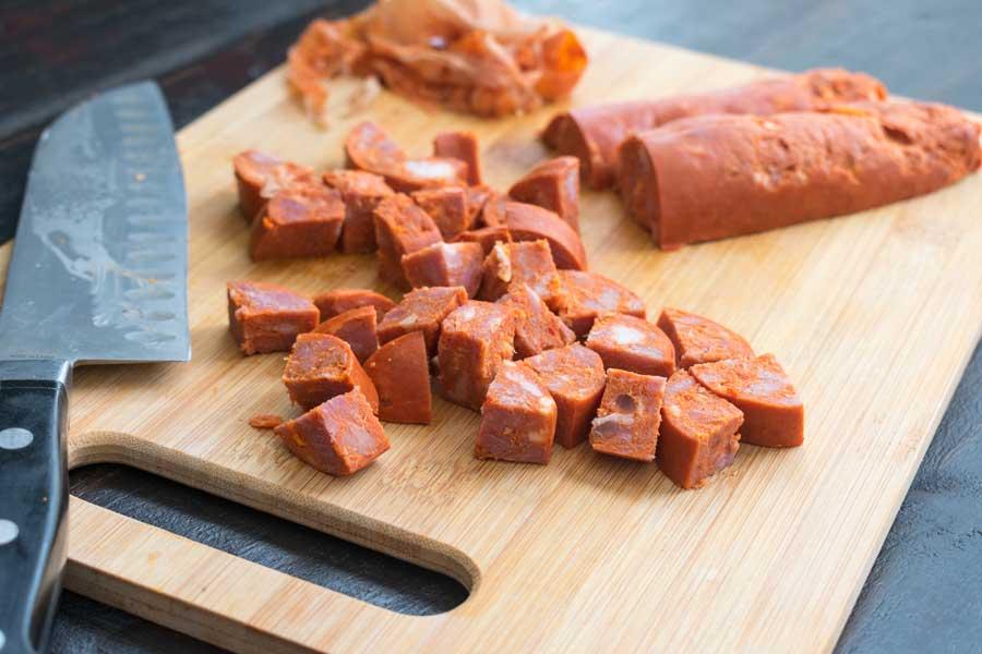 Chopping the linguiça sausage