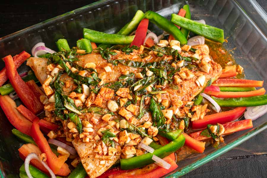 The marinated fish fillet in the baking dish with the bell peppers and shallots